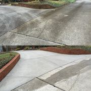 A dirty driveway and brick wall before and after