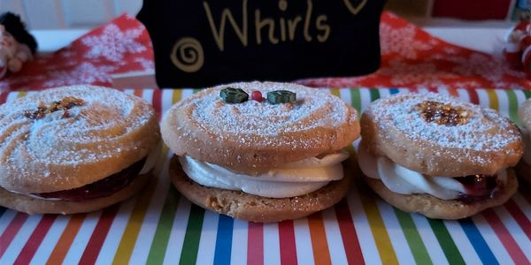 viennese whirl soft cookies sandwiching a buttercream and decorated for Christmas