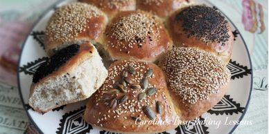 close up of a plate of seeded round rolls