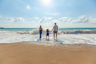 A family walking on the beach holding their child's hands