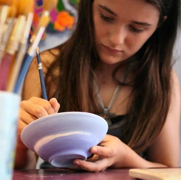 Artist painting pottery bowl