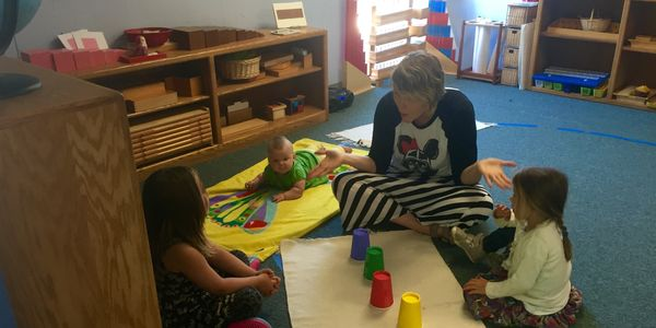 Teacher Mia playing a game with preschool students (and her baby daughter onlooking).
