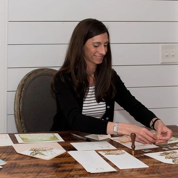 Jessica Armstrong assembling invitations for customers