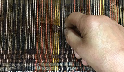 Rolling fabric strip weft to be beaten into warp