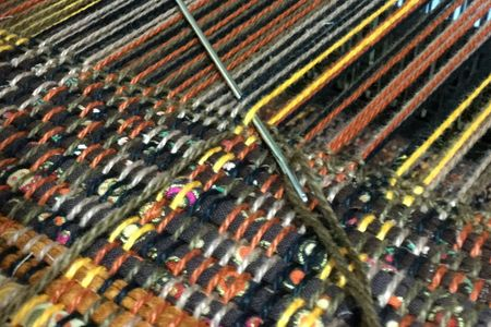 Hemming edge woven fabric while on the loom