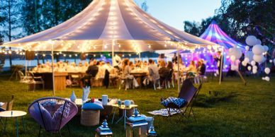 Event tent with white lights, balloons and a dinner setup