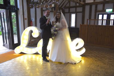 bride and groom in standing in front of love sign