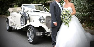 bride and groom standing in front of open top car