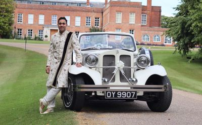 groom standing next to wedding car