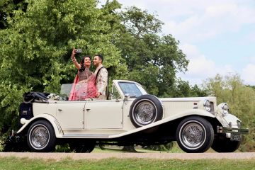 bride and groom standing in open top car
