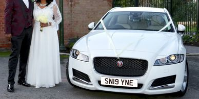 bride and groom standing next to wedding car