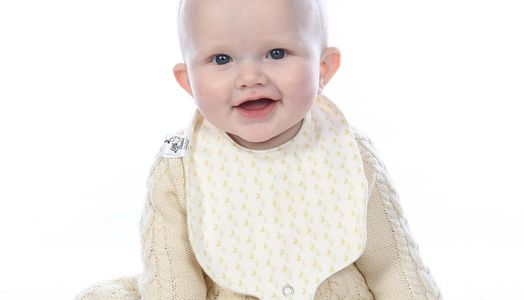 Tiny baby wearing our organic cotton bib with dummy attachment in banana shade