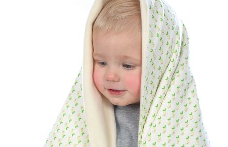Little boy covered in an organic cotton and bamboo baby blanket in Apple shade