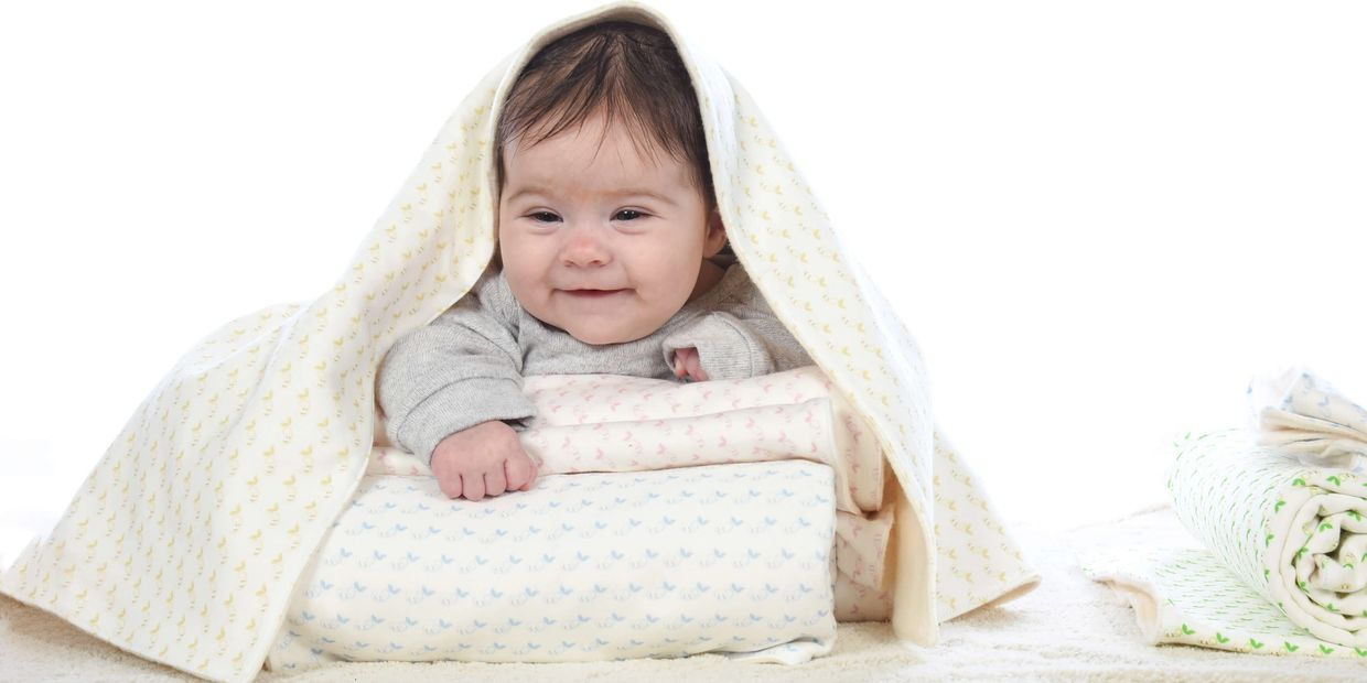 Adorable baby covered in an organic cotton baby blanket with a soft bamboo backing