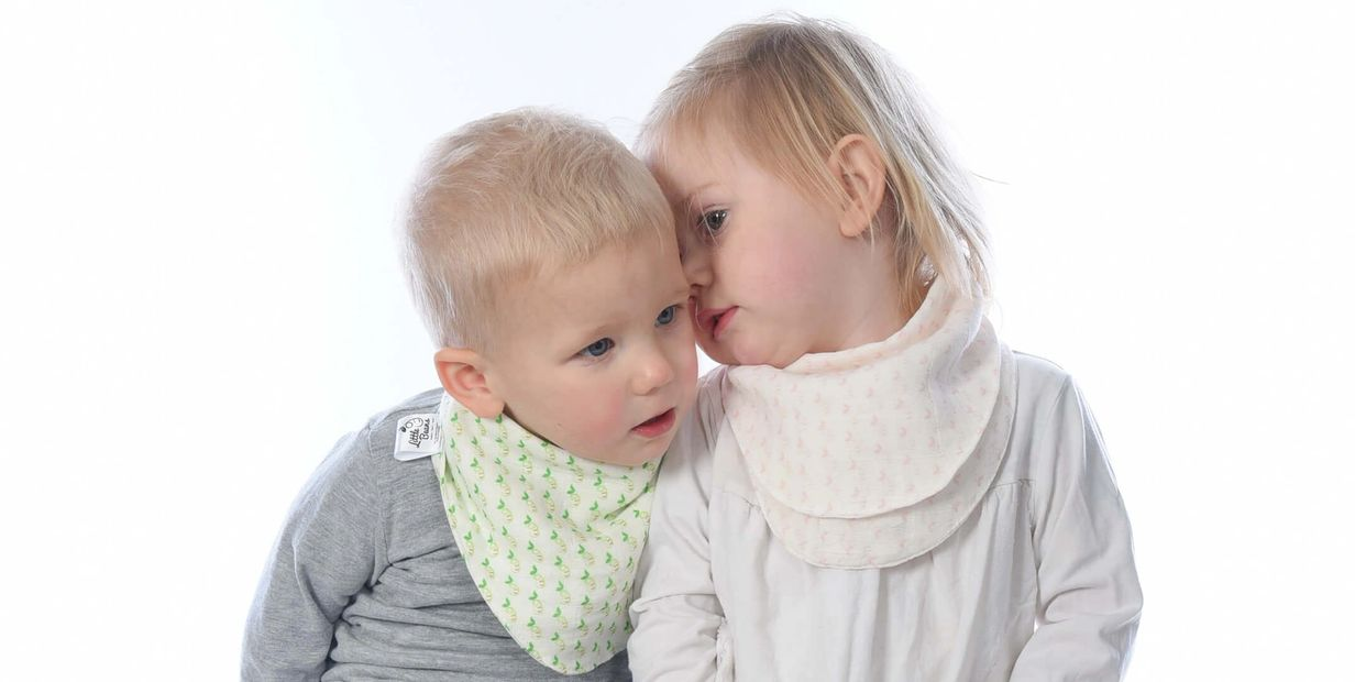 Young boy and girl whispering to each other wearing our organic cotton bibs with little beans signat