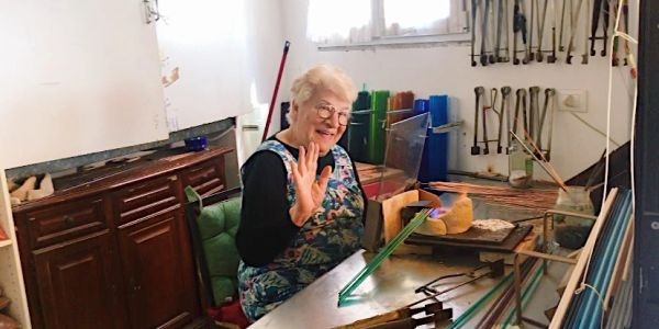 Italian glass maker and artist waving in her workshop and blowing Murano glass beads. Friendly smile