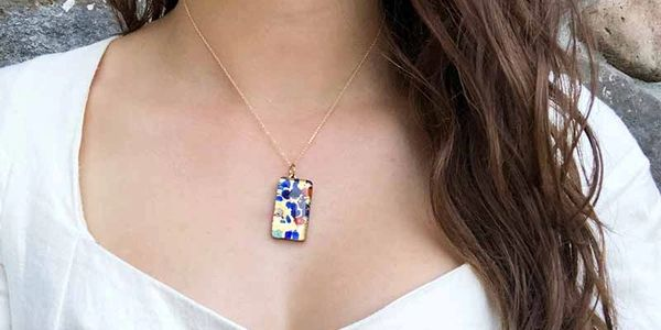 Colorful handmade Murano glass pendant with gold chain on women model with white shirt.