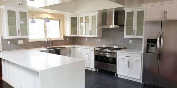 white shaker with design cabinets and free standing hood quartz counter top with water fall glass door cabinets grey backsplash tile , dark grey floor