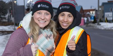 two volunteers giving thumbs up
