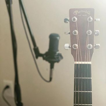Guitar and microphone in a studio.