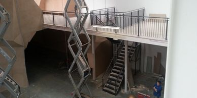 A mezzanine floor with child safe vertical bar balustrade behind an extended scissor lift.