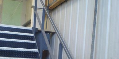 Welded and painted steel double tubular handrail on a steel staircase in a West London unit.