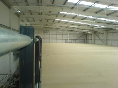 A large expanse of clear mezzanine floor with double tubular handrail in a distribution warehouse.