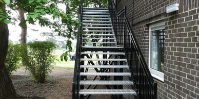 A steel external fire escape staircase powder coated and fitted with galvanised perforated treads.