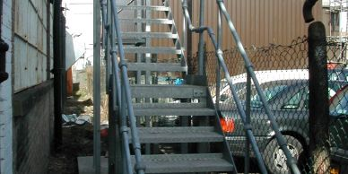 A galvanised steel external fire escape staircase with ball and tube handrail standards in London.