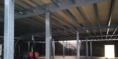 Galvanised steel column casings fitted to the columns of a decked mezzanine floor at a Kent site.