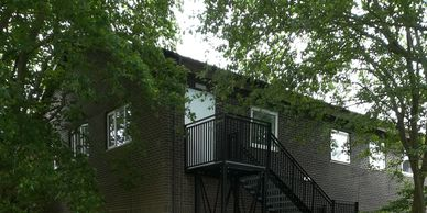 An external fire escape staircase fitted with childsafe vertical bar handrail at a Kent school.