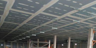 An unpainted taped and jointed MF ceiling viewed from below under an office mezzanine in Essex.