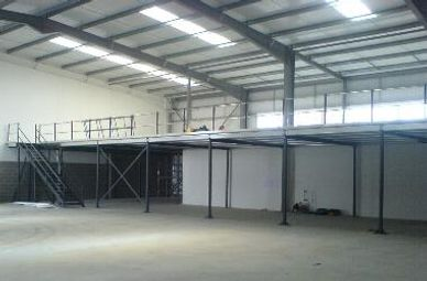 A completed mezzanine floor with exposed columns, main steels , purlins, handrail and staircase.