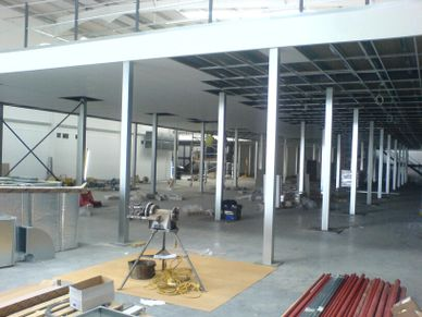 Fire protection of a mezzanine floor with galvanised column casings and a suspended ceiling grid.