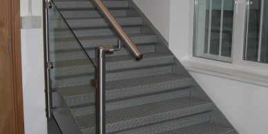 A steel staircase with stainless steel handrail and toughened glass infills in South London.