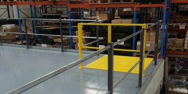 A biparting pallet safety gate with pallet loading plate on an assembly mezzanine floor in Surrey.