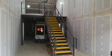 A small mezzanine floor and straight steel staircase with yellow tread nosings and handrail.