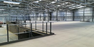 View over a large mezzanine floor, through handrail on its perimeter within a large Kent warehouse.