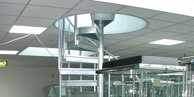 A galvanised steel spiral staircase serving an office mezzanine floor through a circular void.
