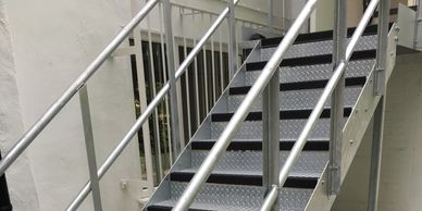 A galvanised steel external fire escape with double tubular handrail and top landing in London.