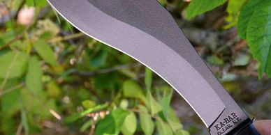 Kabar kukri machete held in front of a camera near foliage.