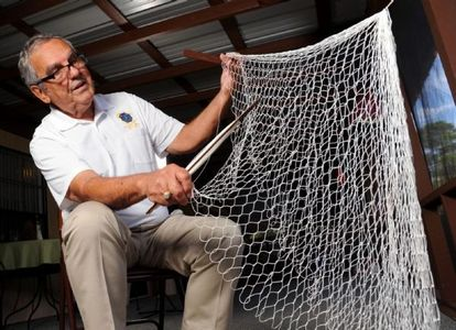 man knitting net. hand made cast nets. handmade castnet