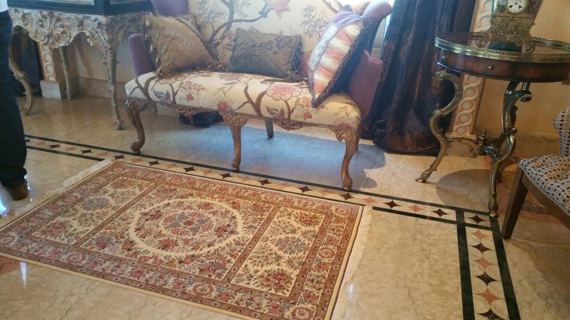 Beautiful Qom silk handmade carpet. This area rug is placed in a hallway with furniture.