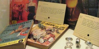 Cufflinks sitting on pulp crime novels by Peter Cheyney rings in front of a book about coffee