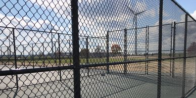 Black vinyl coated chain link fence installed at Ohio Northern University tennis courts.