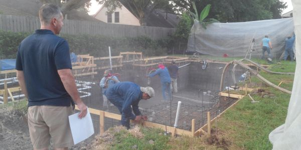 Supervising Gunite crew spraying gunite to create concrete shell of custom residential pool