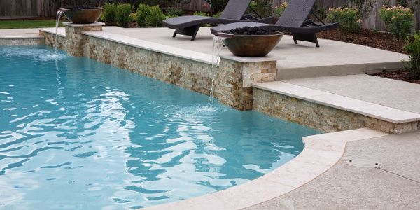 Beautiful custom residential concrete geometric swimming pool with raised deck and water features.