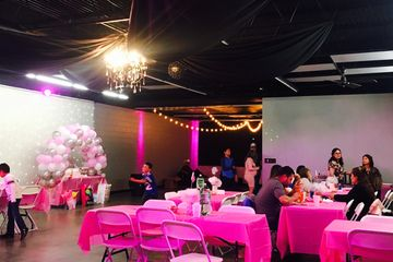 Baby shower with pink lighting and table cloths.