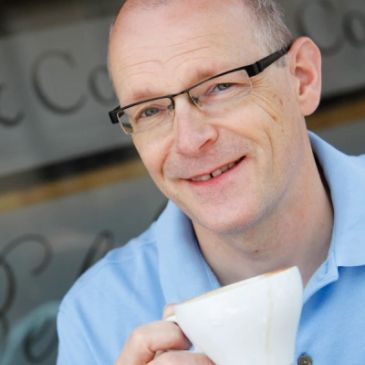 Image of Jonathan Morris raising a coffee cup outside a cafe.