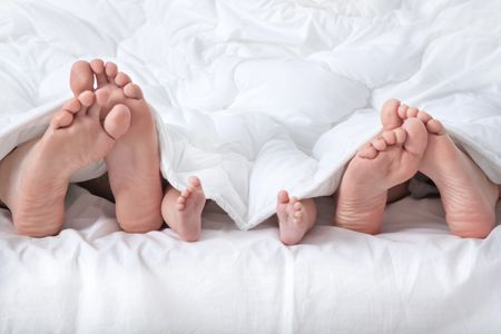 family with feet sticking out from under the covers